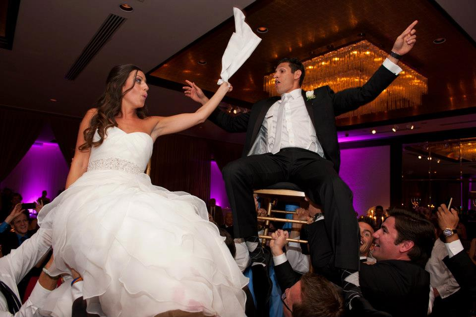 bride and groom on chair for hora at wedding