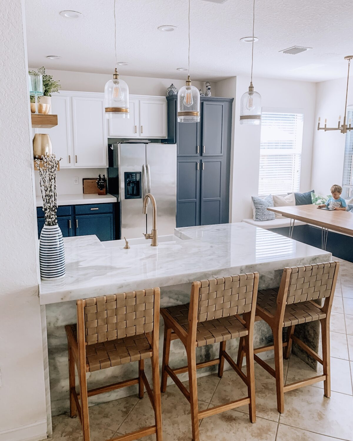 Kitchen before and after, tuxedo cabinets, tan barstools, champagne bronze faucet, blue cabinets, marble island, marble kitchen, Primestones marble Florida